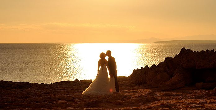 Bride and groom at sunset kissing.